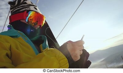 Skier in glasses with mobile phone on chair lift through the...