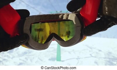 Skier wearing glasses on the background of sky with sun and...