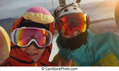 Young couple with snowboarders taking selfie on smartphone in lift in slowmotion. 1920x1080