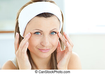 young woman touching her wrinkles standing in her bathroom