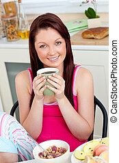 Charming woman eating her breakfast at home holding a cup of coffee in the kitchen