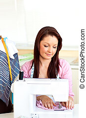 Concentrated caucasian woman sewing at home in the kitchen