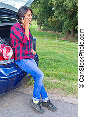 Woman phoning mobile sitting in car trunk outside -...