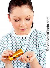 Caucasian female patient holding pills