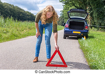 Caucasian woman placing warning triangle on rural road