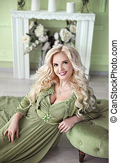 Beautiful smiling blond woman with long curly hair style wears in green dress posing on the floor over decor flowers wall, home interior.