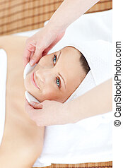 Positive woman receiving a beauty treatment in a spa center