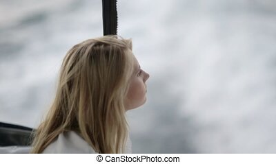 Thoughtful blonde posing in the moving boat in the sea