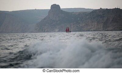 Yacht with red sails in the sea with waves