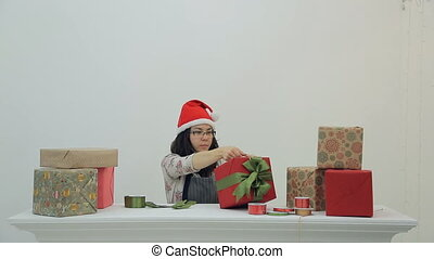 Asian brunette woman sits wraps new year present box in studio