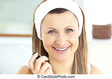 Positive woman applying gloss on her lips in the bathroom