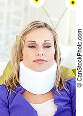 Attractive woman wearing neckbrace lying on a sofa against a...