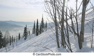 Winter mountains panorama with ski slopes through the sun in...