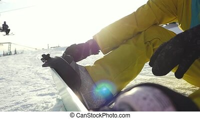 Man sitting on a slope through the sun wears snowboard in...