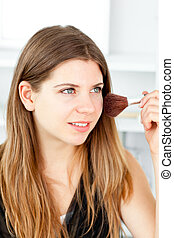 Radiant woman using a powder brush in her bathroom