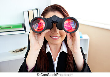 Radiant businesswoman sitting on a chair and looking through binoculars in her office