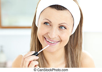 Radiant woman applying gloss on her lips in the bathroom