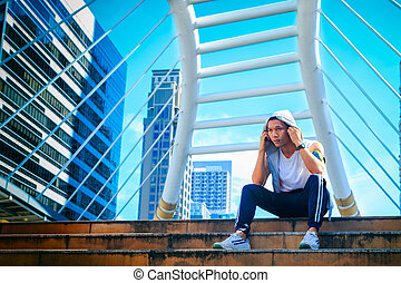 Young man in sports clothing resting outdoors while...