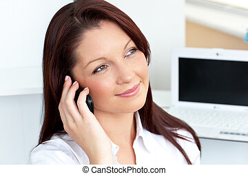 Cheerful businesswoman talking on phone sitting in her...