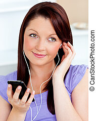 Attractive woman using her cellphone to listen to music with...