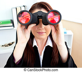 Young businesswoman looking through binoculars sitting at her desk in her office