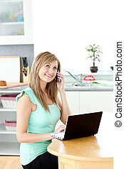 Smiling woman on phone using a laptop in the kitchen