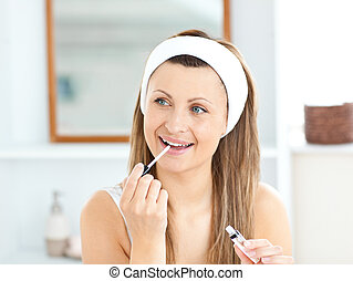 Happy woman applying gloss on her lips in the bathroom