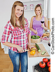 Two smiling women cooking together at home