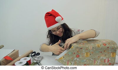 Woman packing present with Gift Wrapping Paper, preparing...