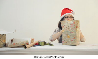 Asian brunette woman sits wraps new year present box in...