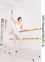 Sporty young woman holding her leg upwards
