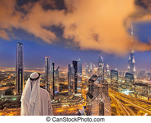 Arabian man watching night cityscape of Dubai with modern futuristic architecture in United Arab Emirates