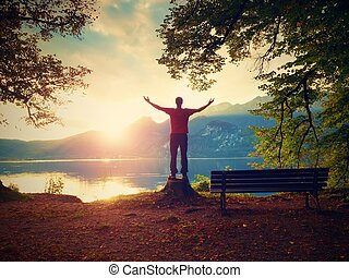 Happy man with rised arms in red t-shirt stand on tree stump...