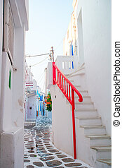 The narrow streets of greek island with balconies, stairs and flowers. Beautiful architecture building exterior with cycladic style.