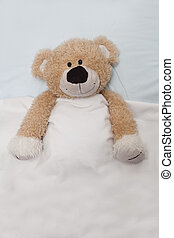 Teddy Bear Laying in Bed - An adorable teddy bear laying in...