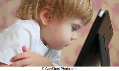child looks cartoons on tablet pc closeup
