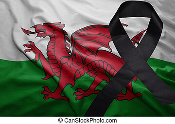 flag of wales with black mourning ribbon - waving national...