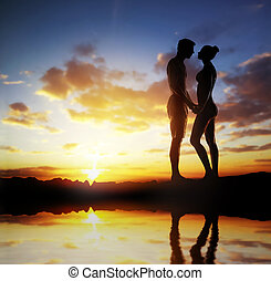 Silhouette of a loving couple over sunset background