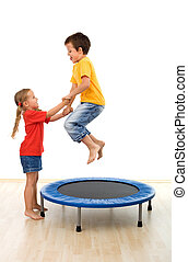 Kids having fun on a trampoline in the gym - helping each...