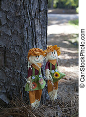 Scarecrow - Pair of small scarecrows by a pine tree