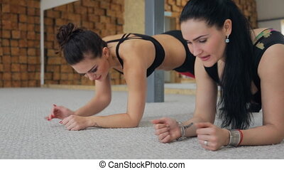 Two fit women doing exercises lying inside fitness studio....