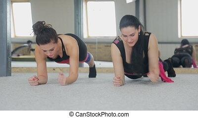 Beautiful women do exercises in gym. Despite intensity of...