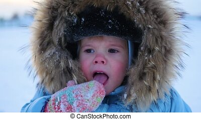 the funny child tries to taste the snow in mittens - the...