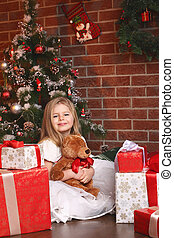 Girl with teddy on Christmas tree background
