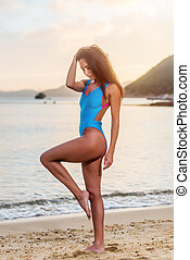 Attractive tanned female tourist in swimwear standing on...