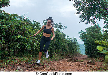 Fitness female athlete running on forest path in mountainous...