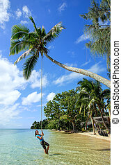 Young woman swinging on a rope swing at Pangaimotu island...