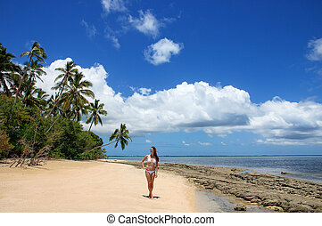 Young woman in bikini standing on the beach of Makaha'a...
