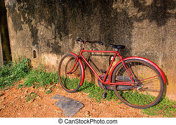 Vintage red bicycle agains the rustic wall
