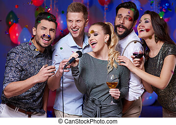 Group of friends singing karaoke at party